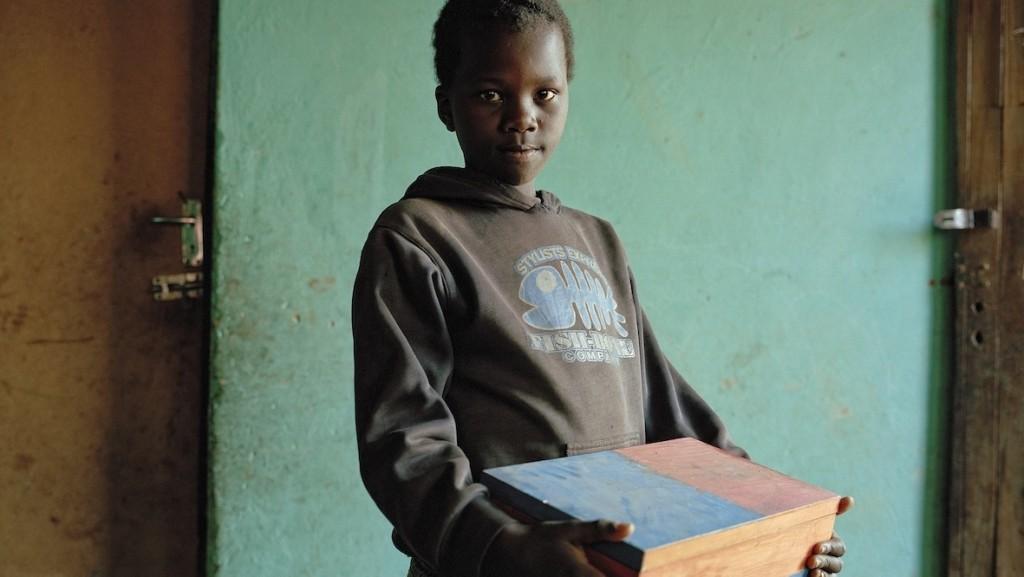"""Contexte:  créé en 1994 à l'école de Religion et de Théologie de l'université du Kwazulu Natal à Pietermaritzburg, le Centre Sinomlando s'est donné pour mission de recouvrir les mémoires silencieuses des communautés chrétiennes et particulièrement de celles qui ont souffert durant les décénies de l'apartheid. Depuis 2001, confronté aux millions d'orphelins que le sida génère à travers tout le pays, le centre a developpé la technique des """"Boites de la Mémoires"""". Cette démarche tente d'offrir aux orphelins la possibilité d'un deuil et ainsi de favoriser leur résilience. Organisé sous la forme de camps (""""children camps""""), ses sessions qui durent 5 jours invitent les enfants à exprimer leurs souvenirs et sentiments (colère, tristesse et abandon) par le bias du dessin, de l'écrit, de la parole collective mais aussi du jeu et du partage d'expérience. A l'issue de ses rencontres, les animateurs du centre remettent à chaque enfant une boite (boite de la mémoire) dans laquelle ils rangeront tous leurs travaux de la semaine et tout ce qu'ils voufront bien y mettre de retour chez eux, faisant de cette boite une sorte de """"tombeau affectif"""" selon l'expression du professeur Boris Cyrulnik. Description image: Sitembiso a 12 ans. Sa mère est morte du sida et son père ne l'a pas reconnu. Il a suivi un camps de Simonlando en avril 2009. Elevé par sa gand mère et sa grande-tante, il pose ici avec sa boite de la mémoire."""